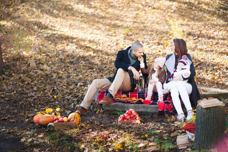 De herfstmanier voor kinderen en de gehele familie Mamma, Papa en twee kinderen op een picknick in de herfst met appelen, pompoen royalty-vrije stock foto