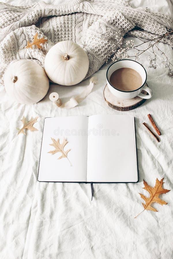 De herfstontbijt in bedsamenstelling Leeg open notitieboekjemodel Kop van koffie, witte pompoenen, sweater, eiken bladeren en royalty-vrije stock afbeeldingen