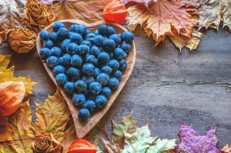 De herfstoogst van blauwe doornen op een houten plaat in de vorm van een hart De achtergrond van de herfst Rode en oranje het bla stock afbeeldingen