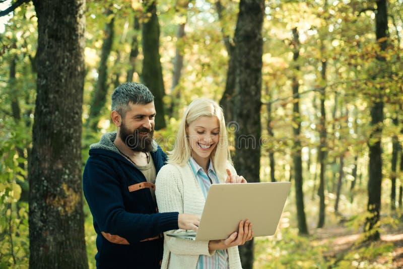 De herfstpaar die notitieboekje gebruiken De herfst openluchtportret van mooi gelukkig meisje en de gebaarde mens die in park of  stock foto