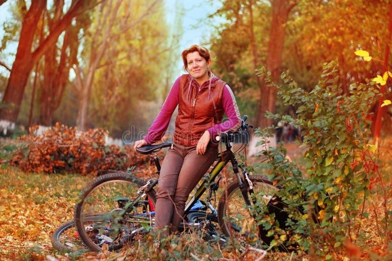 De herfstpark De vrouw geniet van berijdend royalty-vrije stock foto