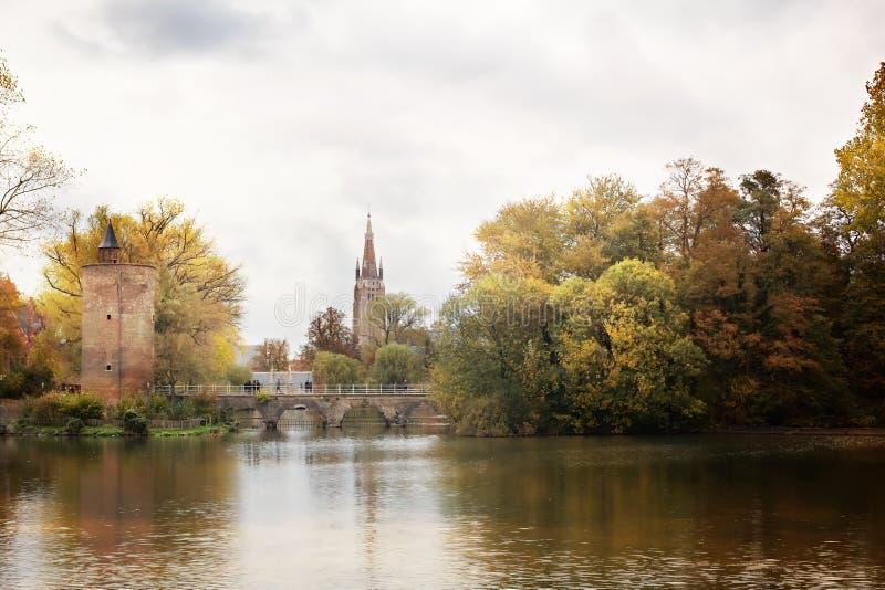 De herfstpark Minnewater en Poertoren-Toren in Brugge stock afbeelding