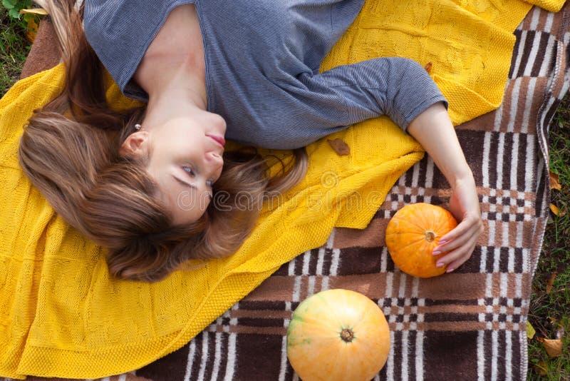 De herfstpicknick, vrouw onder de gele gebreide plaid, pompoenen, hoogste mening stock fotografie