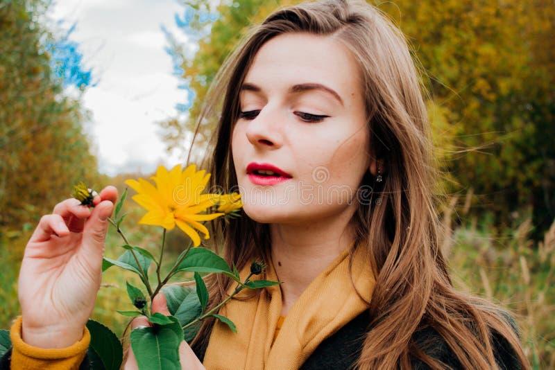 De herfstportret, jong mooi meisje met lang haar in aard met heldere gele bloem stock afbeelding