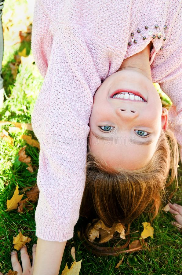 De herfstportret van de aanbiddelijke het glimlachen bevindende bovenkant van het meisjekind - neer op gras en het hebben van pre stock afbeeldingen