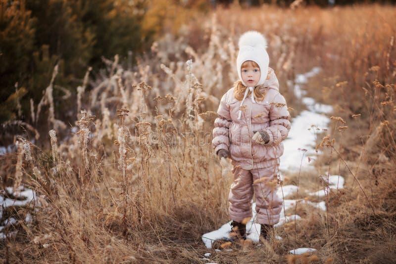 De herfstportret van een meisje in een beige jasje en een witte hoed die op een gebied lopen stock foto's