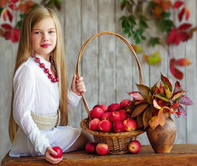 De herfstportret van een meisje met appelen stock foto's