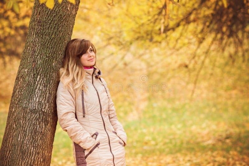 De herfstportret van een mooie vrouw dichtbij een boom, een concept harmonie van de aardmens, een gang in aard royalty-vrije stock foto's