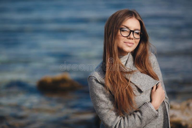 De herfstportret van een mooie vrouw op de overzeese kust royalty-vrije stock foto's