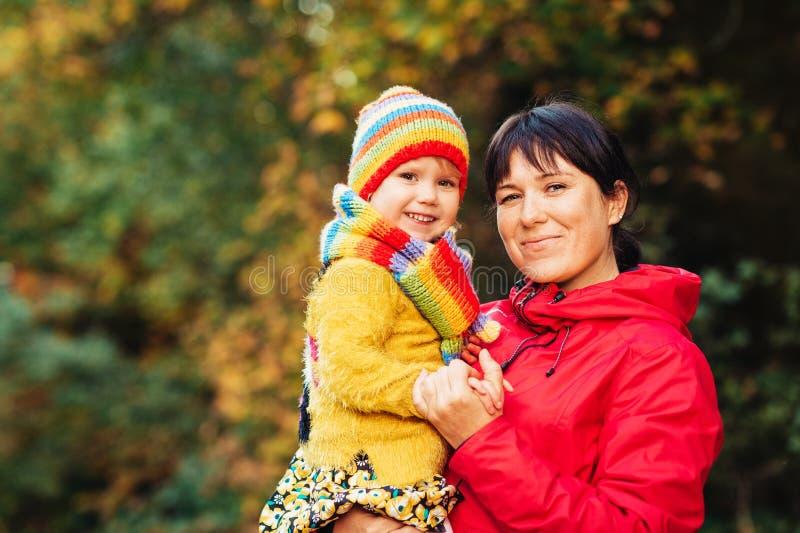 De herfstportret van gelukkige jonge moeder die weinig dochter leuk houden stock foto