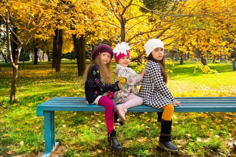 De herfstportret van mooie kinderen op de bank Gelukkige meisjes met bladeren in het park in daling royalty-vrije stock afbeeldingen