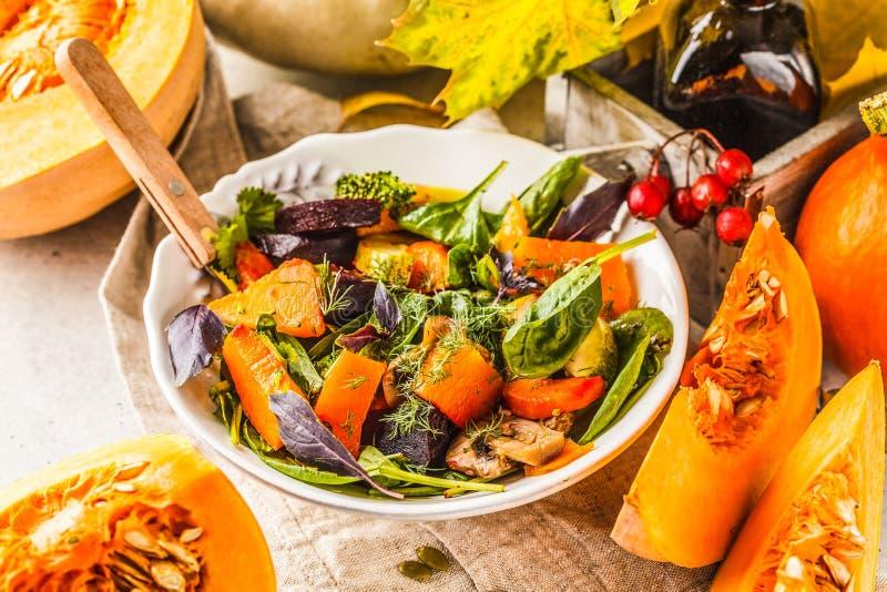De herfstsalade met gebakken pompoen, biet, courgette en wortelen Het gezonde concept van het veganistvoedsel royalty-vrije stock afbeelding