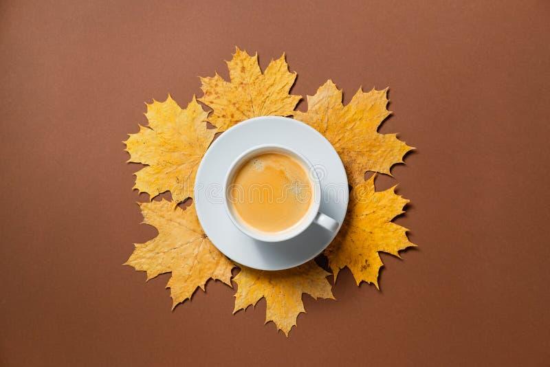 De herfstsamenstelling, dalingsbladeren, hete stomende kop van koffie op bruine achtergrond royalty-vrije stock afbeeldingen