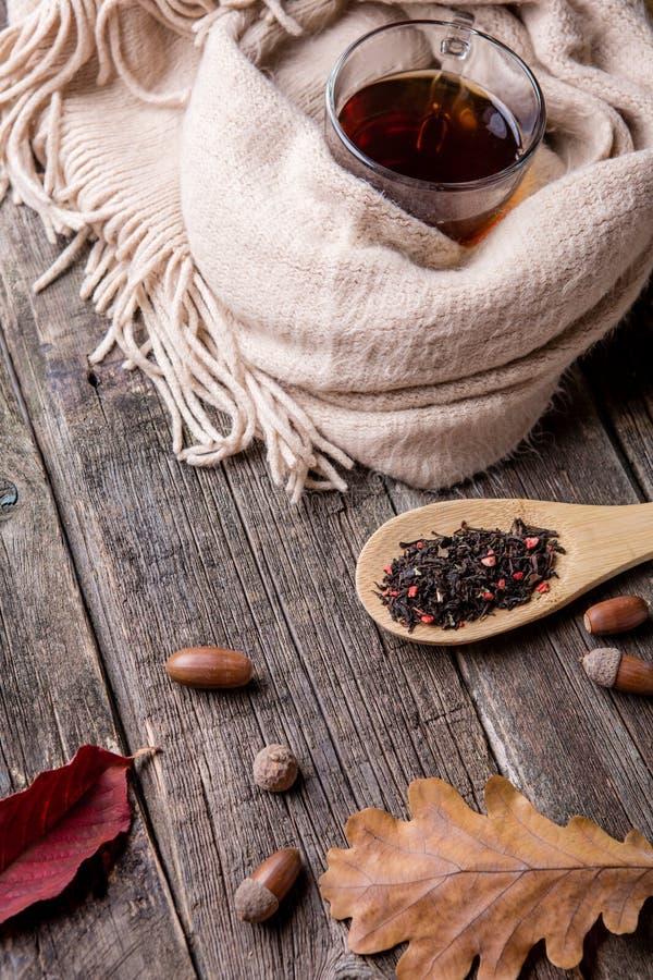 De herfstsamenstelling, glaskop thee en een warme sjaal op houten lijstachtergrond stock afbeeldingen