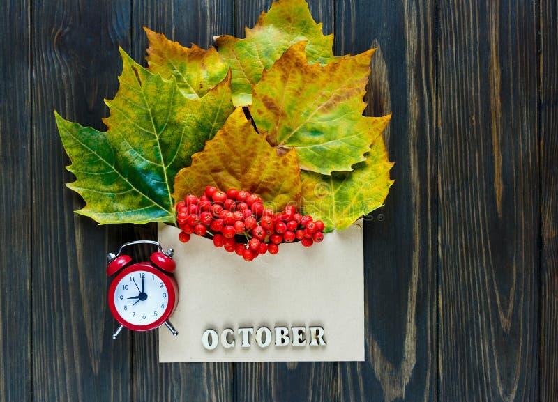 De herfstsamenstelling met envelop en bladeren, bessen daarin naast woord Oktober per brieven, rode klok en kop van koffie royalty-vrije stock afbeeldingen