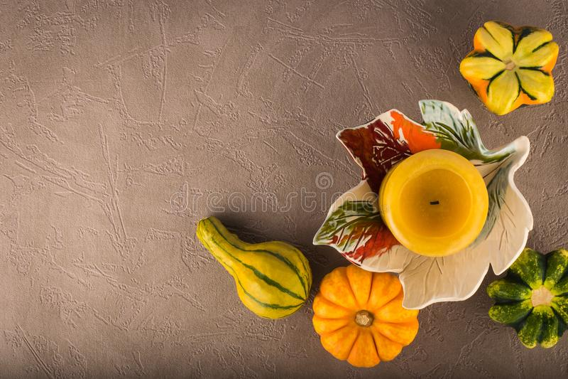 De herfstsamenstelling van decoratieve pompoenen en kaars stock afbeelding