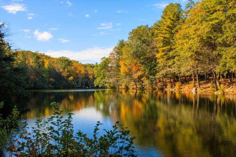 De herfstscène in Burr Pond wordt weerspiegeld dat stock afbeeldingen