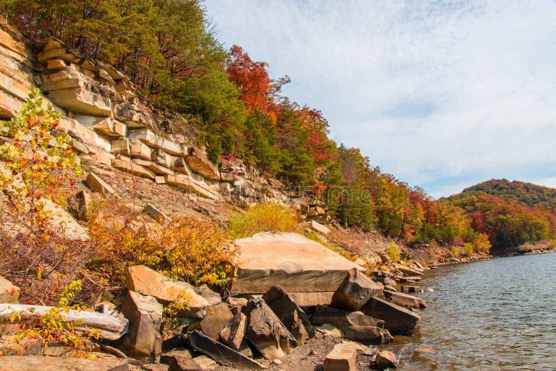 De herfstseizoen bij meer met mooi bos bij rotsachtige heuvelkust royalty-vrije stock foto's