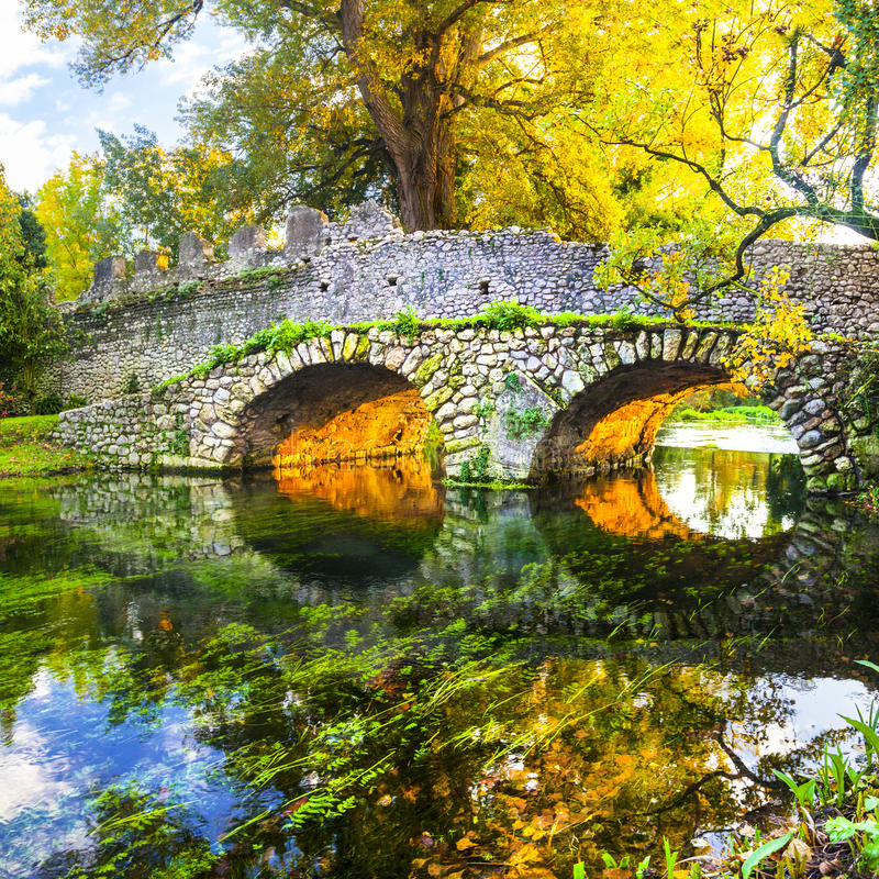 De herfststemming - oude brug in Ninfa-park royalty-vrije stock foto's