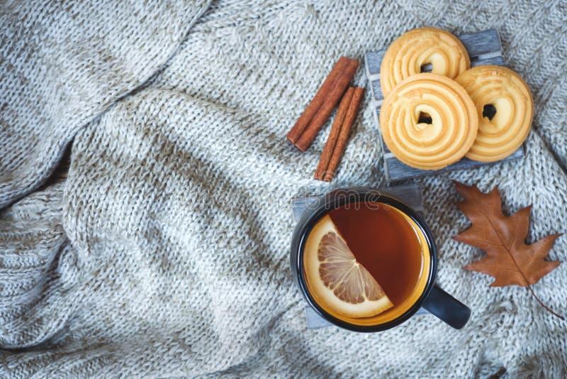 De herfststilleven met kop thee, koekjes, sweater en bladeren op een warme zachte deken concept de comfortabele herfst, dalingsse stock afbeelding