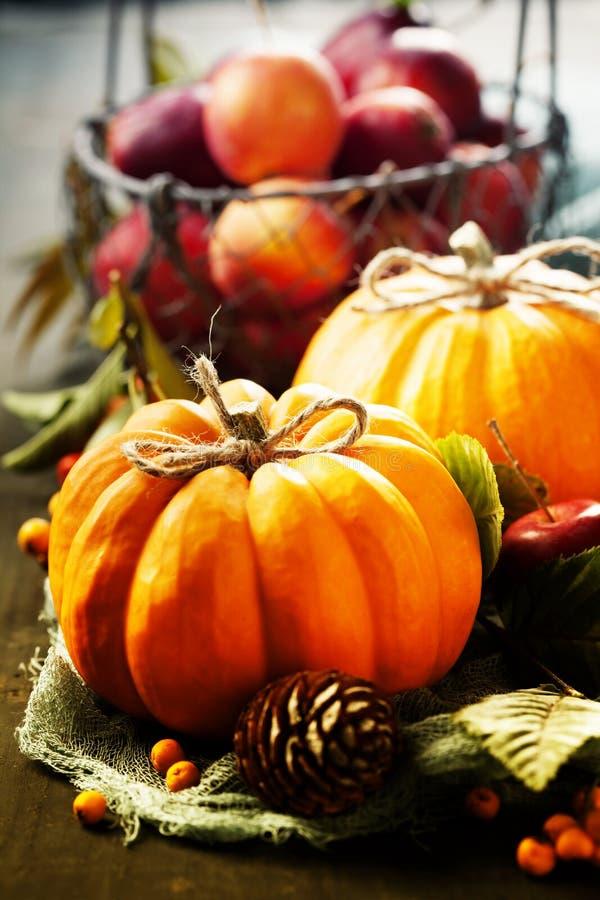 De herfststilleven met pompoenen, appelen en bladeren op oude houten achtergrond royalty-vrije stock afbeeldingen