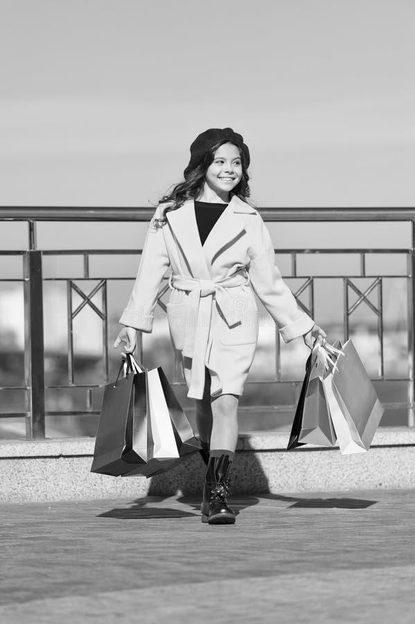 De herfsttendens meisje met aankoop in het winkelen zakken Het winkelen dag Gelukkig meisje De jong geitjemanier ziet eruit styli stock foto