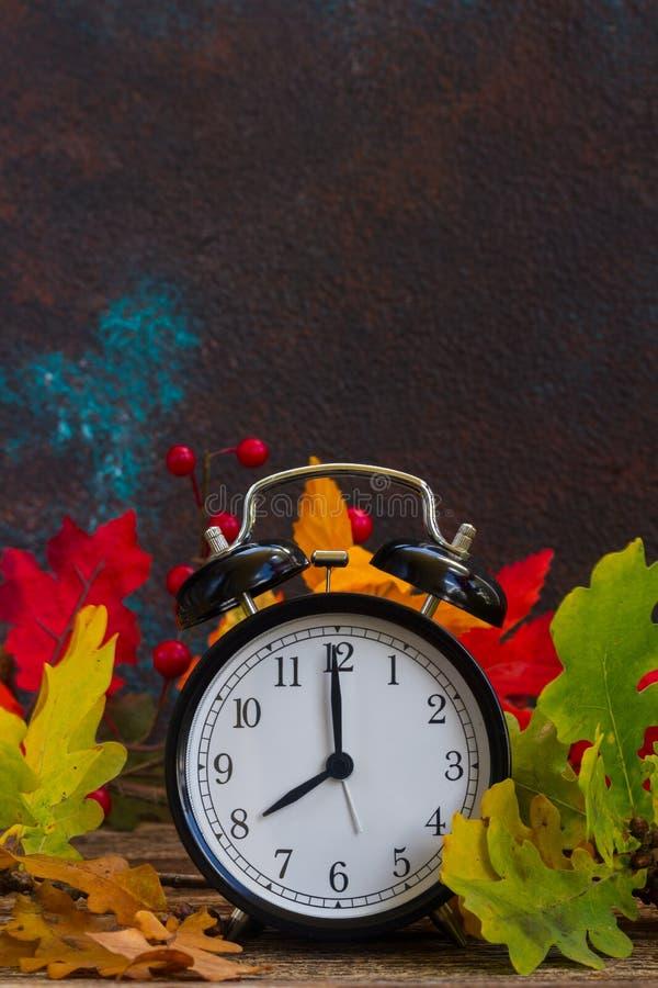 De herfsttijd - dalingsbladeren met klok stock afbeelding