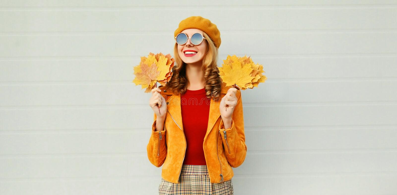 De herfsttijd! mooie glimlachende vrouw die met gele esdoornbladeren weg op stadsstraat kijken over grijze muur stock foto