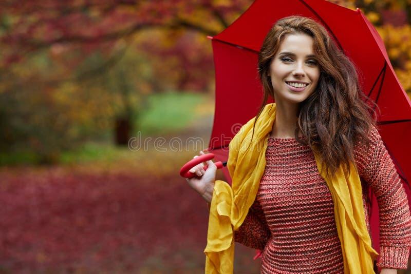 De herfstvrouw in de herfstpark met rood paraplu, sjaal en leer stock afbeelding