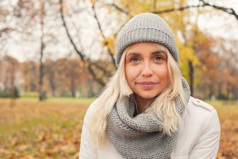 De herfstvrouw in grijze gebreide hoed en sjaal in openlucht stock foto