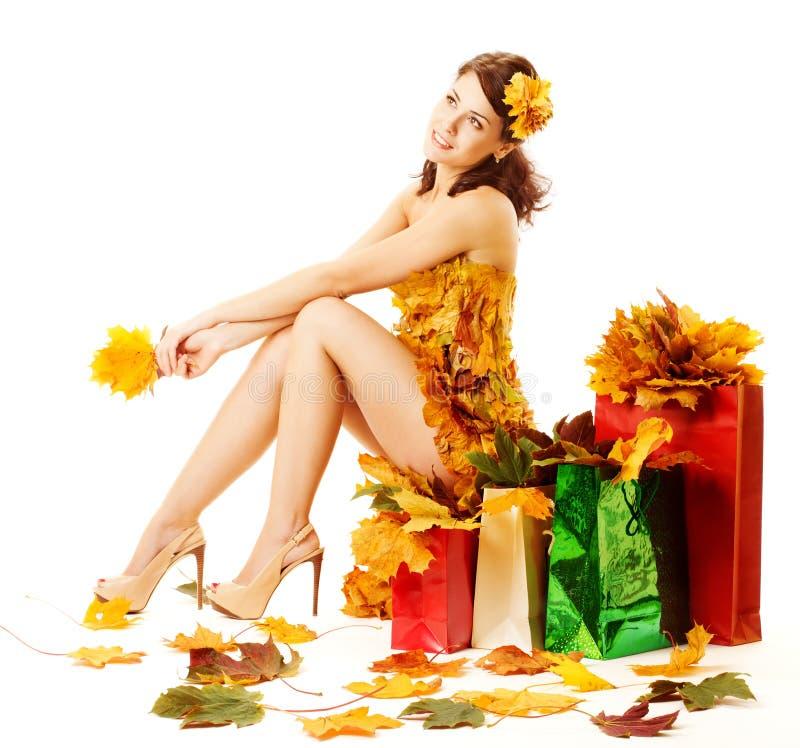 De herfstvrouw, het winkelen zakken met gele esdoornbladeren stock fotografie