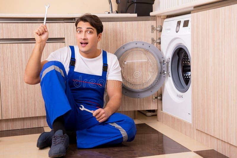 De hersteller die wasmachine herstellen bij keuken stock fotografie