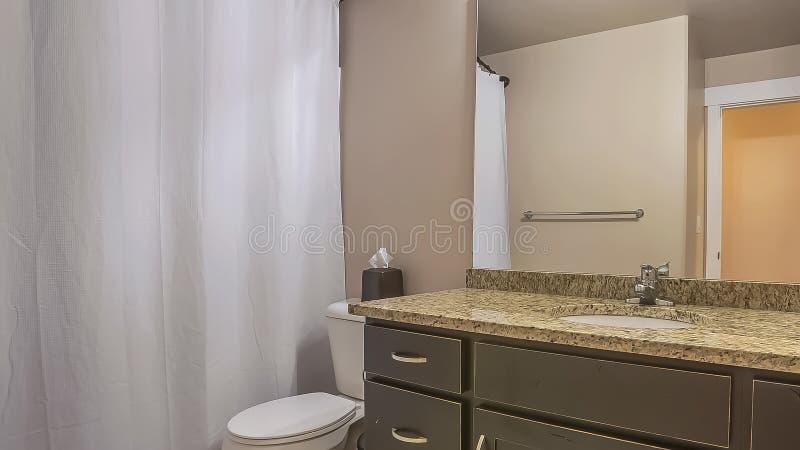 De het de eenheidstoilet en handdoek van de panoramaijdelheid haken tegen de witte muur van een goed aangestoken badkamers vast royalty-vrije stock afbeelding
