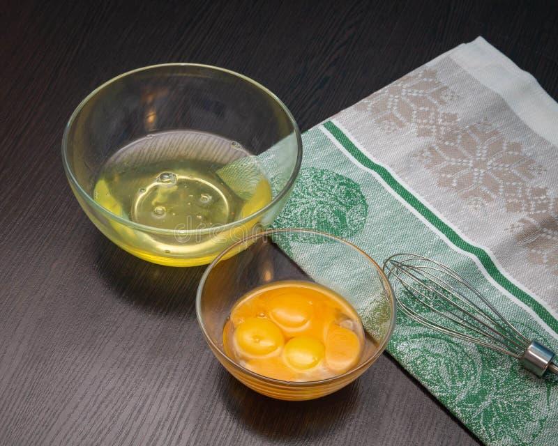 De het eiwit en dooiers in transparante glaskoppen met zwaaien daarna stock foto's