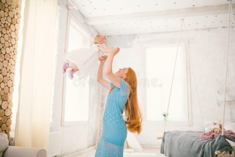 De het familiemamma en dochter één éénjarige onderhouden zich binnen het binnenland De vrouw zet de kind` s wapens op en duwt haa royalty-vrije stock fotografie