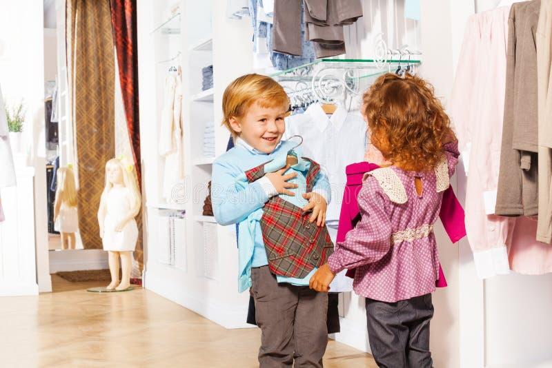 De het glimlachende vest van de jongensmontage en sweater van de meisjesholding stock afbeelding