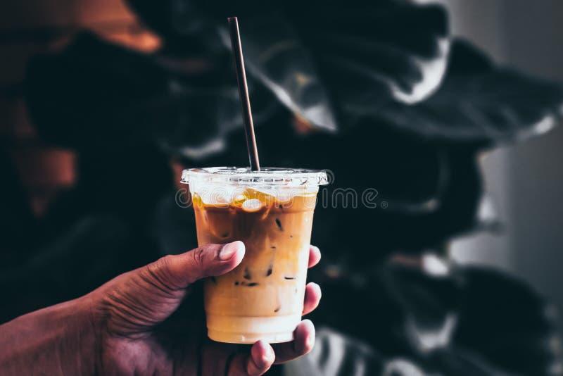 De het Ijskoffie van de handgreep in een lang glas met room goot over en koffiebonen op een donkere toon van het aard groene verl stock afbeelding