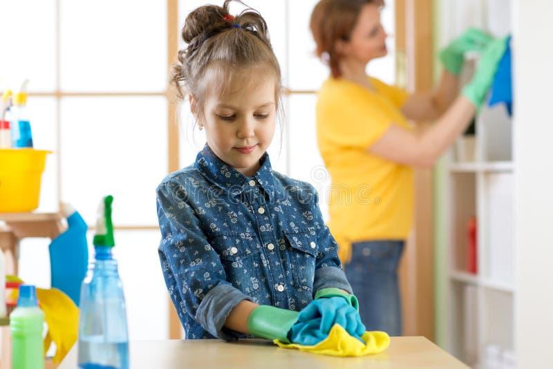 De het jong geitjemeisje en moeder maken thuis het schoonmaken in ruimte stock foto