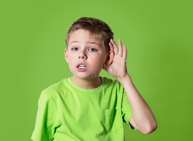 De het kindhoorzitting van het close-upportret iets, ouders spreekt, roddels, hand aan oorgebaar op groene achtergrond wordt geïs royalty-vrije stock foto