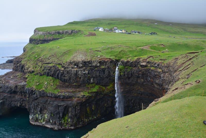 De het kleine Dorp en Waterval van Gasadalur stock afbeeldingen