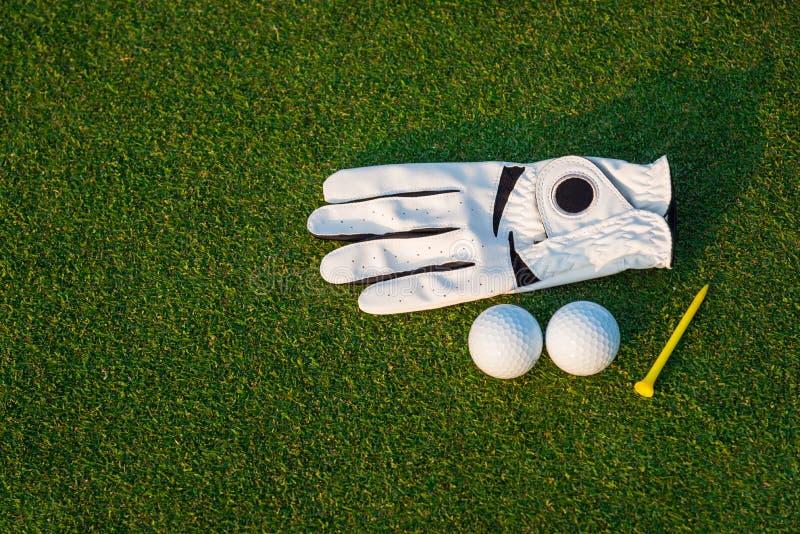 De het materiaal witte handschoen van de golfsport, de golfbal, de golfclub en het gele T-stukgolf met groen gras royalty-vrije stock afbeeldingen