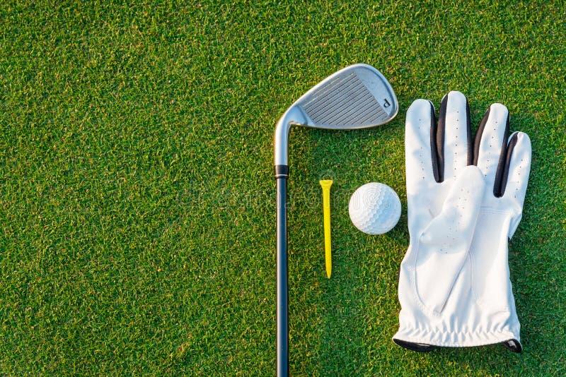 De het materiaal witte handschoen van de golfsport, de golfbal, de golfclub en het gele T-stukgolf met groen gras stock afbeeldingen