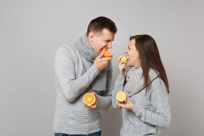 De het meisjeskerel van het pretpaar in grijze sweaters, sjaals houdt samen oranje die citroen op grijze muurstudio wordt geïsole royalty-vrije stock foto