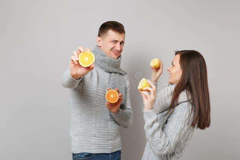 De het meisjeskerel van het pretpaar in grijze sweaters, sjaals houdt samen oranje die citroen op grijze muurstudio wordt geïsole stock foto's