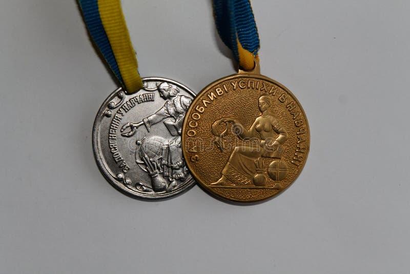 De het oude goud en zilveren medailles van de Oekraïne voor voortreffelijkheid in middelbare schoolgraduatie stock afbeeldingen