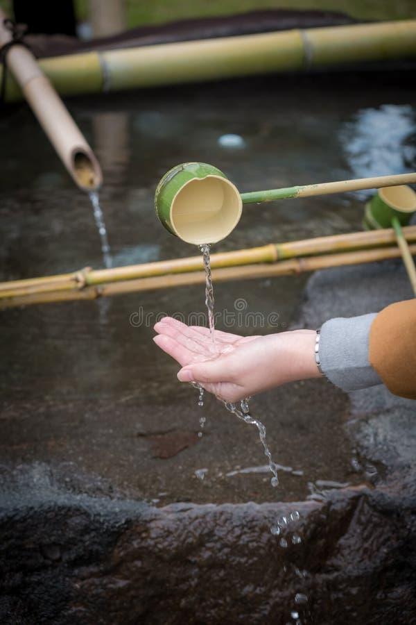 De het reinigen van Shinto Omairi ceremonie door te gebruiken water in bamboelepel vóór gaat aan tempel in Japan binnen stock afbeeldingen
