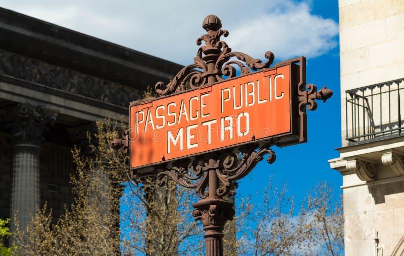 De het Rode metro van Parijs teken en kerk van Madeleine op de achtergrond stock foto