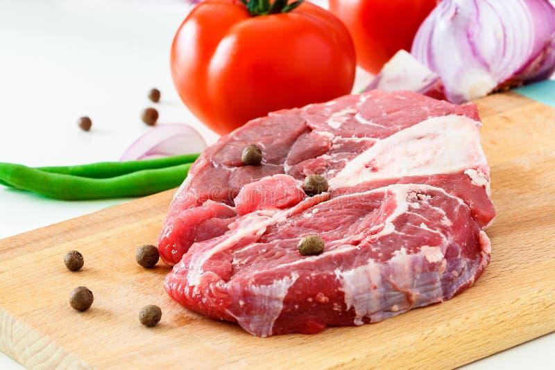 De het ruwe lapje vlees en groente van het vleesrundvlees op houten scherpe raad Dicht p stock fotografie