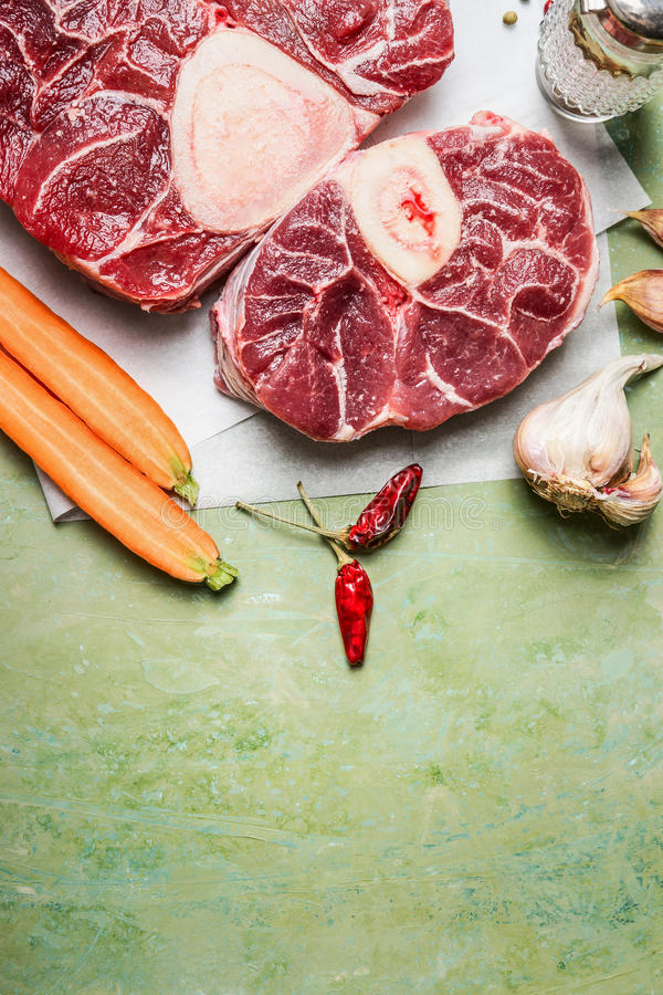De het ruwe vlees en ingrediënten van de kalfsvleessteel voor het koken van Osso Buco op rustieke achtergrond, hoogste mening stock fotografie