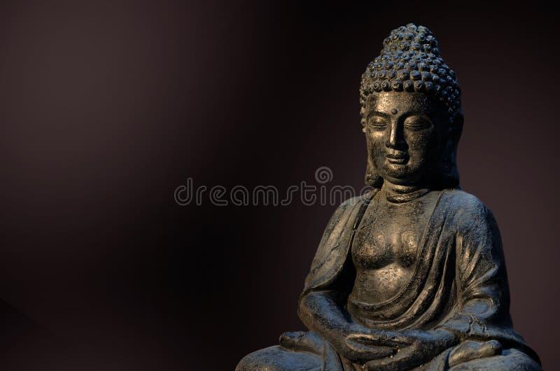 De het standbeeldzitting van Boedha in meditatie stelt tegen diepe donkere achtergrond stock afbeeldingen